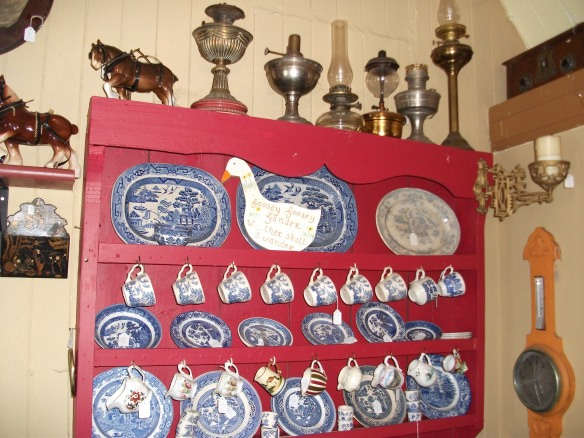 Shelves filled with oddments of willow pattern crockery